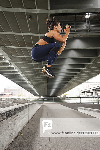 Fit Woman Doing A Jump Tuck Outside In The City