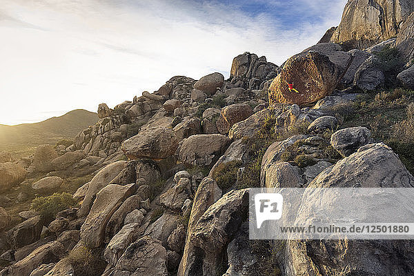 Distant View Of A Climber Bouldering On Rock In Desert Landscape