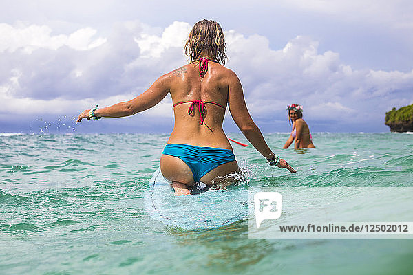 Surfer girl in ocean water.