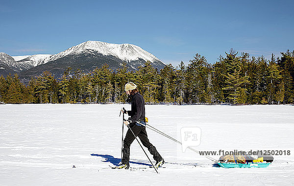 A Man Cross Country skies across a frozen lake while pulling a pulk sled. In the background can be seen Mount Katahdin.