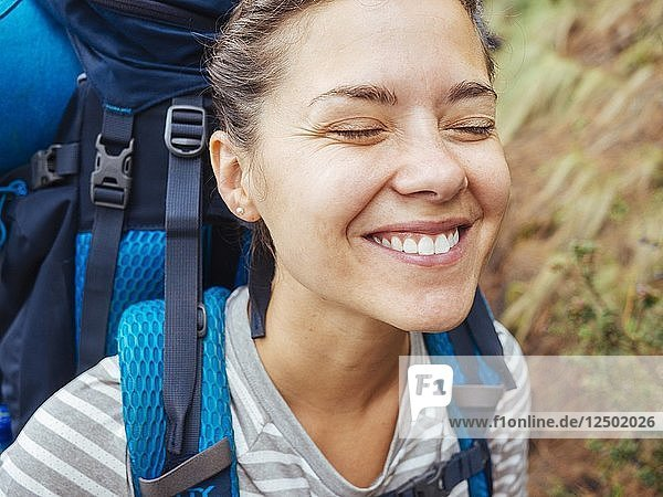A Smiling Woman With A Backpack Hiking In The Forest