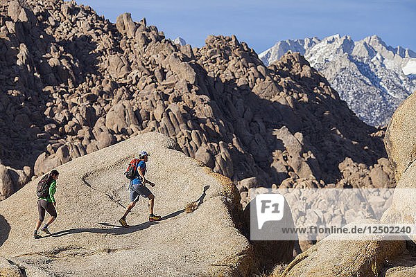 A man and woman rambling around on giant boulders in the Alabama Hills at the foothills of the Sierra Nevada Mountains outside Lone Pine  California.