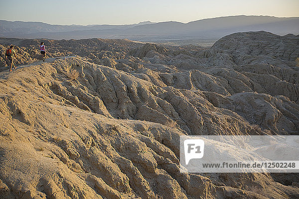 A man and woman taking in the view of sunset in the Badlands in the Anza-Borrego Desert  California.