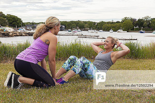 Two women doing sit-up partner workout outside on the grass near the water