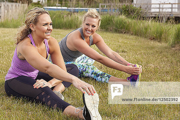 Two women stretching in the grass and smiling