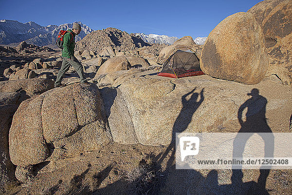 Man and woman doing shadow play by campsite in Alabama Hills