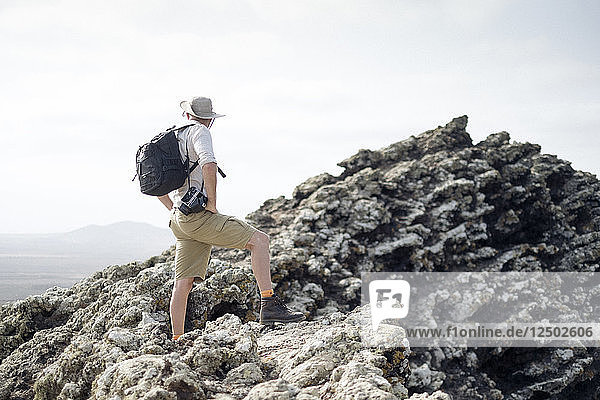 A Man Stands On Top Of A Volcanic Rock With A Camera In Hand