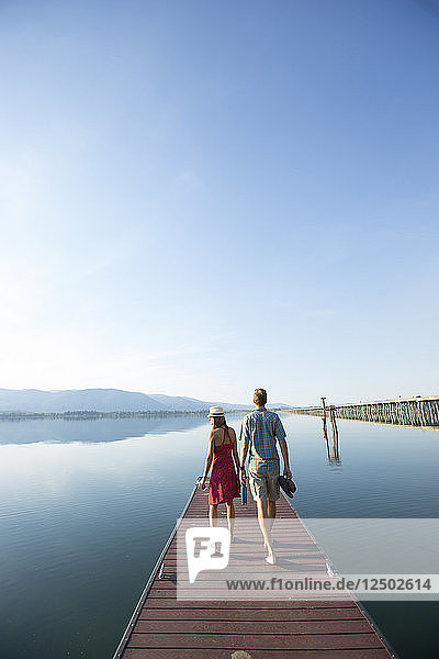 Rear View Of Couple Walking On Dock Overlooking Lake Pend Oreille  Sandpoint  Idaho