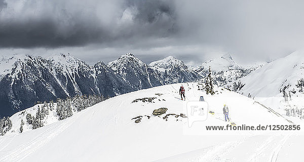 A group of climbers drag sleds of gear over the snow at Artist Poing in the Mount Baker Backcountry.