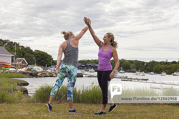 Two female friends giving a high-five in workout clothes