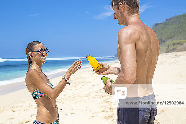 Young man giving a juice to her girlfreind