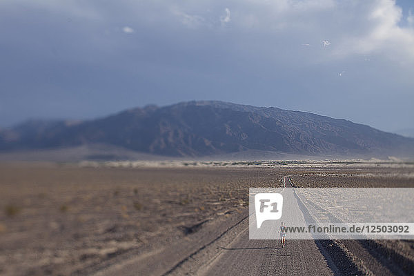 Long Exposure Of Woman Running On Dirt Road In Death Valley National Park