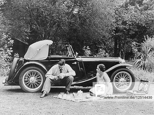 Couple having a picnic by an MG TA Midget  late 1930s. Artist: Unknown