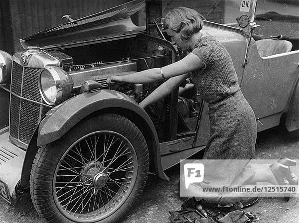 Kitty Brunell working on her MG F Magna. Artist: Unknown