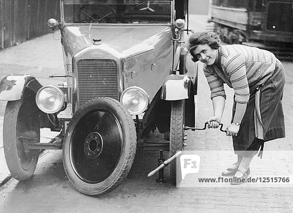 Ivy Cummings changing a tyre on a 1925 Singer 10/26  London  c1925. Artist: Unknown