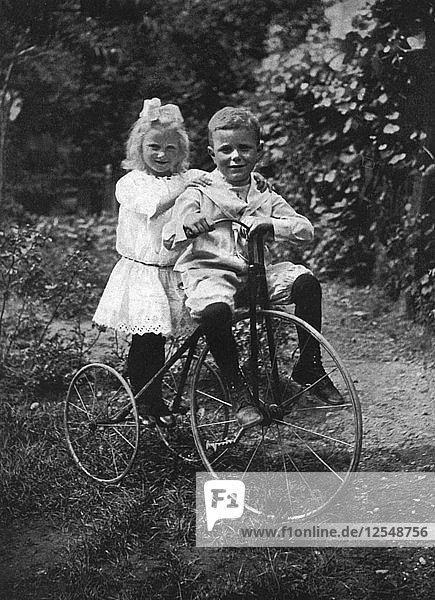 Two children on a tricycle  1911-1912.Artist: CW Perry