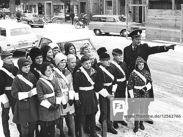A policeman teaches a group of schoolchildren how to be traffic officers  Sweden  c1956-1969(?). Artist: Unknown