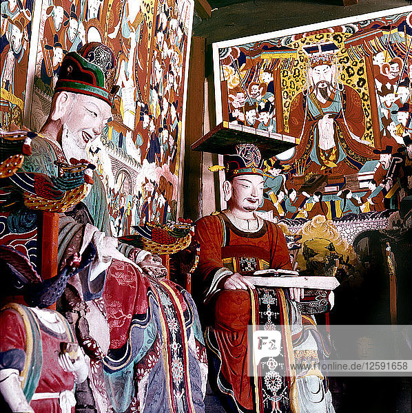 Thankas and statues of Taoist sages or monks inside the temple on Diamond Mountain.