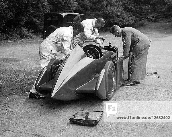 Mechanics working on Leon Cushmans Austin 7 racer for a speed record attempt  Brooklands  1931. Artist: Bill Brunell.
