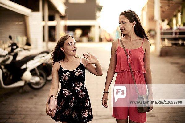 Two women walking in streets of holiday destination Chersonisoss  Crete  Greece