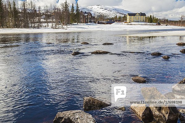 View from Wassara river on Mount Dundret in background  ice on the river and snow on the mountain at spring season  Gällivare  Swedish Lapland  Sweden.