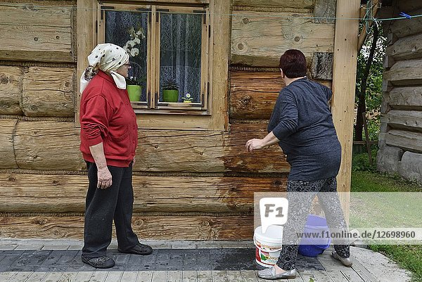 Village women washing their wooden house at Chocholow  Podhale region  Malopolska Province (Lesser Poland)  Poland  Central Europe.