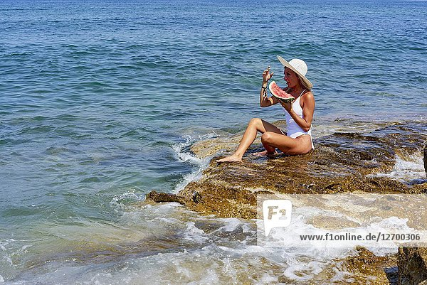 Woman with water melon sitting on rock next to sea  holiday  summer  sunny  enjoying life  travel  healthy. Chersonissos  Crete  Greece.