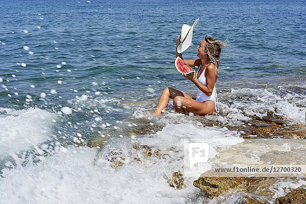 Woman with water melon and sunhat sitting on rock in sea  water splashes  excitement  holiday  vacation  summer  adventure. Chersonissos  Crete  Greece.