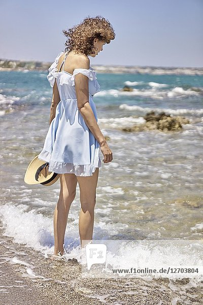 Woman on beach  wearing dress  sunhat  summer  in Hersonissos  Crete  Greece