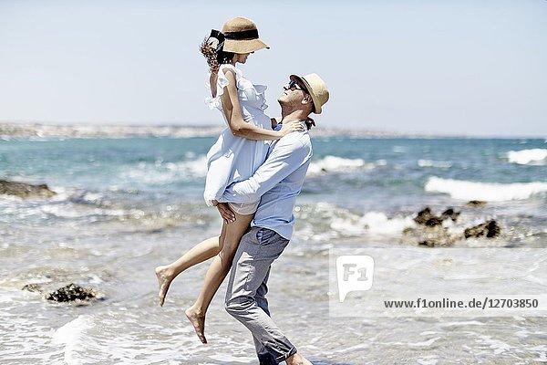 Man carrying woman at beach  love  couple  dating  honeymoon  in Hersonissos  Crete  Greece