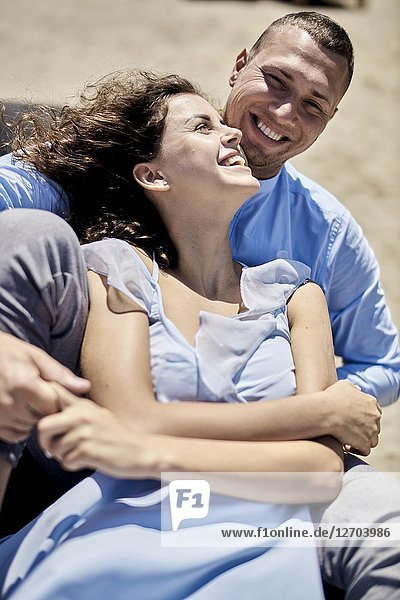 Couple sitting on sunbeds at beach  vacations  summer  love  playful  togetherness  happiness  candid  unposed