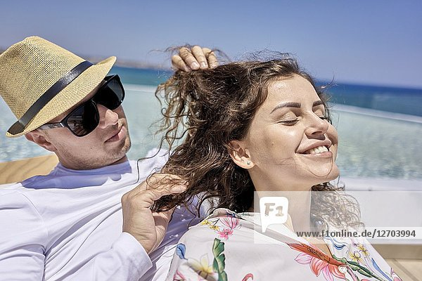 Lovers  man caressing hair of woman  holiday  summer  couple  pool