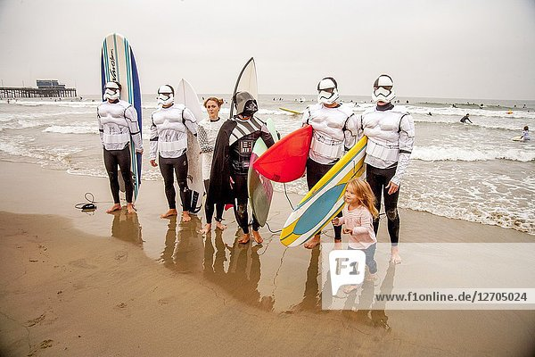Wearing fanciful Star Wars costumes and hefting their surfboards  men and women and head for the ocean at a Halloween costumed surfing event in Huntington Beach  CA  accompanied by a little girl.