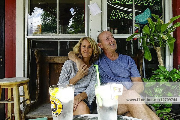 Sharon  Connecticut  USA A couple enjoying a moment together on the porch of a local bar.