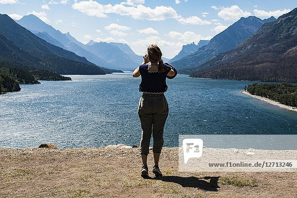 A young woman takes photos in Waterton Lakes National Park  southern Alberta  Canada.