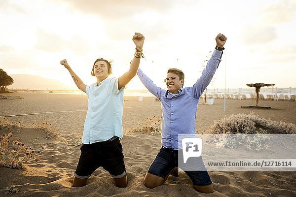 Two young men kneeling on beach  wearing business shirts  in holiday destination Malia  Crete  Greece