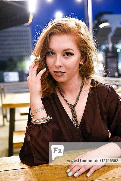 A pretty 25 year old redheaded woman looking at the camera sitting at an outdoor cafe.