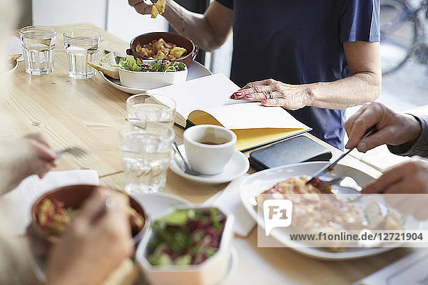 Friends having food while sitting with book at table in restaurant