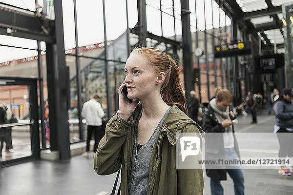 Young woman talking on mobile phone with friend in background at city