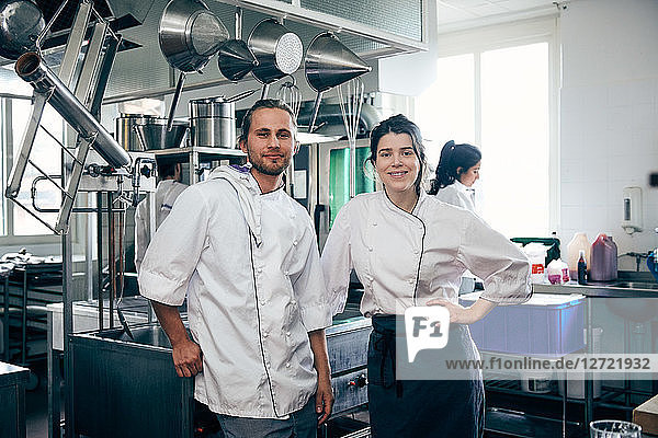 Portrait of confident chefs standing in commercial kitchen