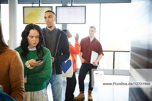 Male and female students standing in queue at university