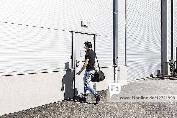 Full length of young man entering warehouse