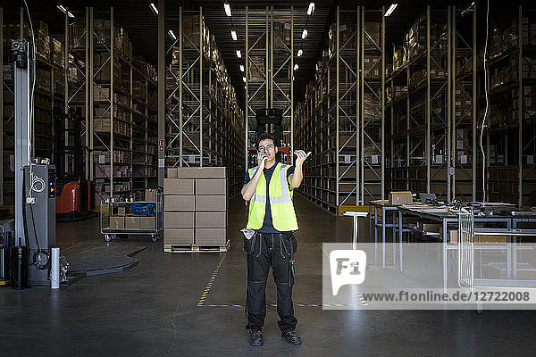 Full length of young male warehouse worker gesturing while using walkie-talkie at storage room