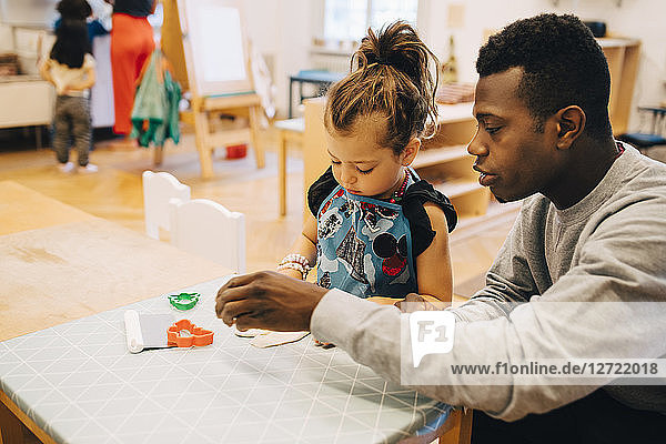 Mid adult male teacher playing with girl at table in child care classroom