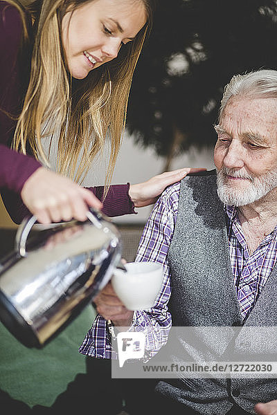 Young woman pouring drink in cup being held by grandfather in nursing home