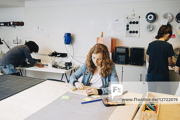Confident female technician working on wood at workbench with colleagues in office