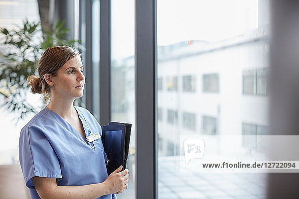Thoughtful female nurse with digital tablet looking through window while standing in corridor at hospital