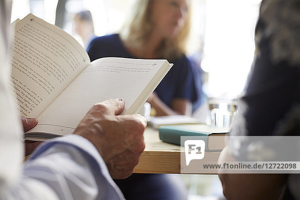 Cropped image of senior man reading book while sitting with friends at restaurant