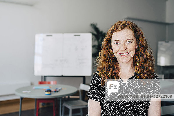Portrait of confident redhead businesswoman standing at creative office