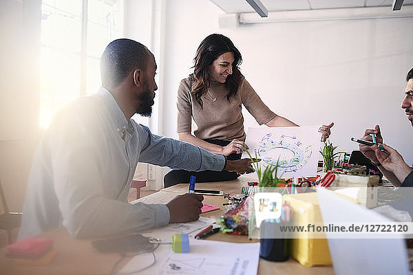 Multi-ethnic male and female engineers discussing over diagram at table during meeting in office